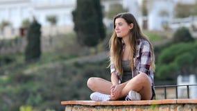 Gelukkige tiener die meningen van een richel overwegen stock videobeelden