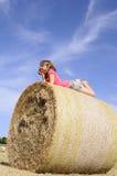 Gelukkige tiener die pret op hooibalen heeft Royalty-vrije Stock Fotografie