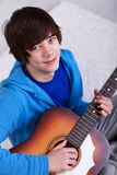 Gelukkige tiener met gitaar stock foto