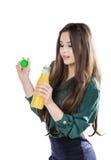 Gelukkige tiener terwijl het houden van een fles jus d'orange in een groene blouse Geïsoleerd op een witte achtergrond stock afbeeldingen