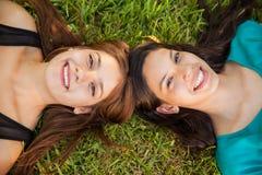 Gelukkige tienerjaren die bij een park ontspannen Stock Afbeelding
