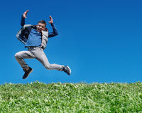 Gelukkige tienerjongen die op weide springen stock foto