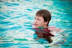 Gelukkige tienerjongen in zwembad met getotene lippen stock afbeelding