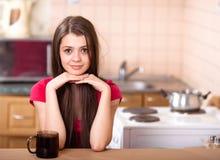 Gelukkige tienermeisje het drinken koffie thuis Stock Afbeeldingen