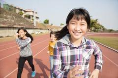 Gelukkige tienermeisjes die op het spoor lopen royalty-vrije stock afbeelding