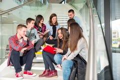 Gelukkige tienermeisjes en jongens op de de tredenschool of universiteit Royalty-vrije Stock Foto's