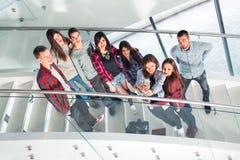 Gelukkige tienermeisjes en jongens op de de tredenschool of universiteit Stock Afbeelding