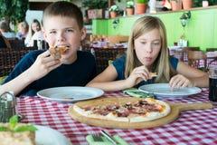 Gelukkige tieners die pizza in een koffie eten Vrienden of siblings die pret in restaurant hebben royalty-vrije stock afbeeldingen