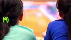 Gelukkige tieners die tennis op sport op slimme TV letten stock videobeelden