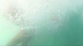 Gelukkige tieners die van schip aan overzees springen en camera, outoors bekijken stock footage