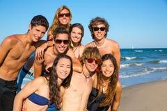 Gelukkige tieners jonge groep samen op strand Stock Afbeeldingen