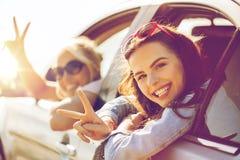 Gelukkige tieners of vrouwen in auto bij kust Stock Afbeeldingen