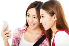 gelukkige tienerstudentenmeisjes die op de slimme telefoon letten royalty-vrije stock foto