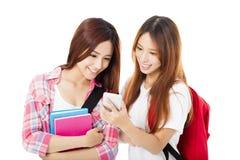 gelukkige tienerstudentenmeisjes die op de slimme telefoon letten stock fotografie