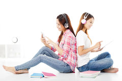 gelukkige tienerstudentenmeisjes die op de vloer zitten stock foto's