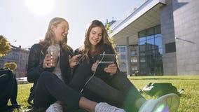 Gelukkige tienervrienden die de computerzitting van de tabletcomputer op het gazon in park in centrum van de stad gebruiken Vrien stock footage
