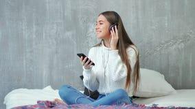 Gelukkige tienervrouw die genietend het luisteren van muziek die smartphone en hoofdtelefoons met behulp van die op bed zitten gl stock videobeelden
