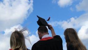 Gelukkige toekomst van gediplomeerden, drie studenten die academische kappen omhoog in de lucht werpen stock videobeelden