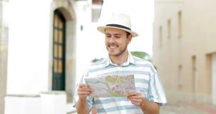 Gelukkige toerist die kant bekijken en een gids raadplegen stock videobeelden