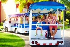Gelukkige toeristenfamilie die van vakantie genieten terwijl het berijden in voertuig door het hotelgebied De dienst van het verv royalty-vrije stock afbeelding