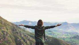 Gelukkige toeristenreiziger die zich op een rots met opgeheven handen bevinden, wandelaar die aan een vallei hieronder in reis in royalty-vrije stock foto