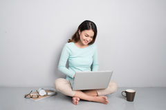 Gelukkige toevallige mooie Aziatische vrouw die aan een laptop zitting o werkt royalty-vrije stock foto's