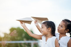 Gelukkige twee Aziatische kindmeisjes die met stuk speelgoed document vliegtuig spelen Stock Afbeeldingen