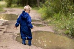 Gelukkige twee jaar oude jongens die op modderige vulklei in rubberlaarzen springt royalty-vrije stock foto's