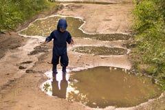 Gelukkige twee jaar oude jongens die op modderige vulklei in rubberlaarzen springt stock afbeeldingen