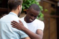 Gelukkige twee multiraciale mannelijke beste vrienden die het omhelzen begroeten op vergadering stock foto's