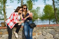 Gelukkige twee vrouwelijke vrienden die op foto's, video's op smartphone letten en pret hebben stock afbeelding
