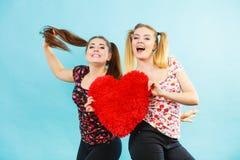 Gelukkige twee vrouwen die hart gevormd hoofdkussen houden stock fotografie
