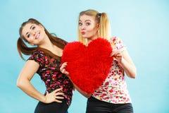 Gelukkige twee vrouwen die hart gevormd hoofdkussen houden royalty-vrije stock afbeeldingen