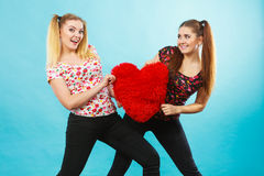 Gelukkige twee vrouwen die hart gevormd hoofdkussen houden stock afbeeldingen