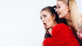 Gelukkige twee vrouwen die hart gevormd hoofdkussen houden stock afbeelding