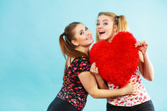 Gelukkige twee vrouwen die hart gevormd hoofdkussen houden stock foto's