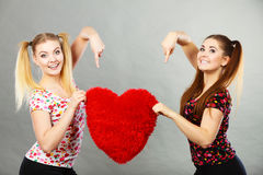 Gelukkige twee vrouwen die hart gevormd hoofdkussen houden royalty-vrije stock fotografie