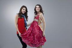 Gelukkige twee vrouwen die rode bloemkleding proberen Royalty-vrije Stock Foto's