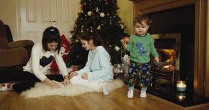 Gelukkige twee zusters Kerstmis en Nieuwjaarboom verfraaien en leuke appel eten en zoon die dichtbij open haard in camera kijken stock videobeelden