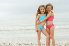 Gelukkige tweelingen bij het strand Stock Foto's