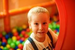 Gelukkige uitdrukking die van het kind` s gezicht, in de kinderen` s ruimte spelen stock foto's