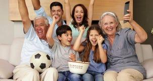 Gelukkige uitgebreide familie het letten op voetbal op TV stock video