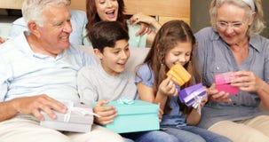 Gelukkige uitgebreide familie het openen giften op de laag stock videobeelden