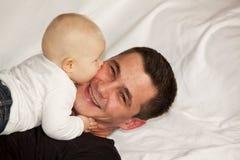 Gelukkige vader die door zijn babymeisje wordt gekust Royalty-vrije Stock Foto's