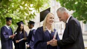 Gelukkige vader die gediplomeerde dochter gelukwensen die haar handen houden dichtbij universiteit royalty-vrije stock fotografie