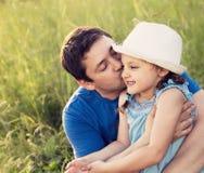 Gelukkige vader die haar lachende dochter in hoed op de zomergree kussen stock afbeelding