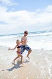 Gelukkige vader en dochter die langs strand lopen Royalty-vrije Stock Foto's
