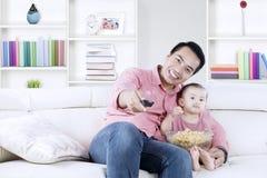 Gelukkige vader en dochter die op TV letten stock foto