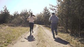 Gelukkige vader en dochterjogging in vroege bos4k stock footage