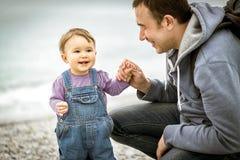 Gelukkige vader en het éénjarige kind spelen op het strand Stock Afbeeldingen